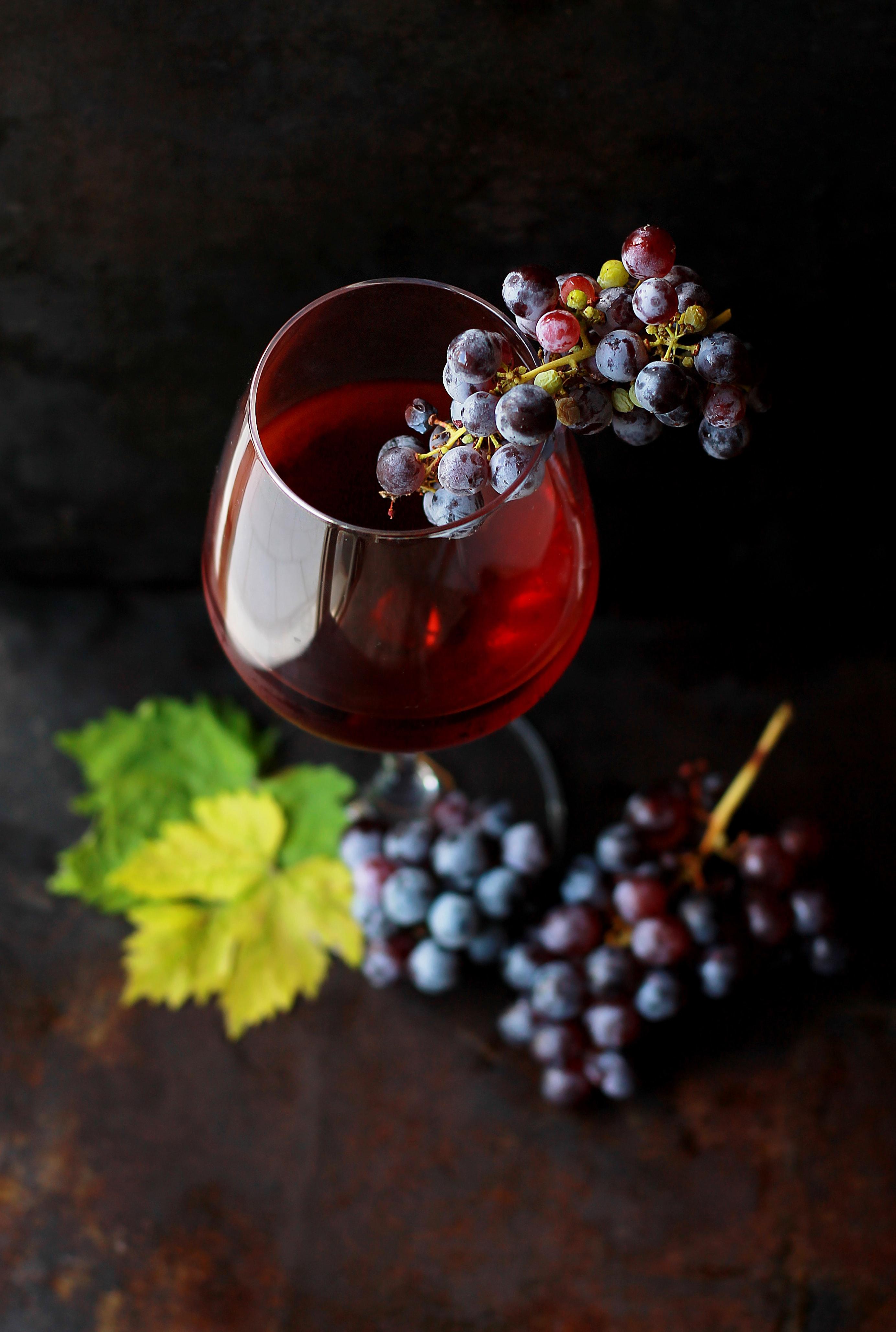 снимка на чаша с вино и пъшки грозде