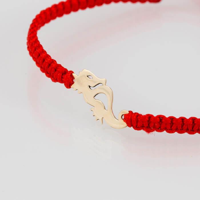 Гривна плетена  с червен конец жълто злато морско конче
